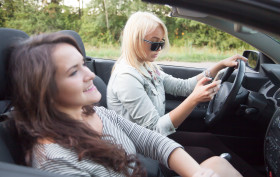 Two beautiful traveler young women friends riding black sports car together, focus on serious busy driver blond lady holding black steering wheel and cellphone, looking at screen, using app, messaging